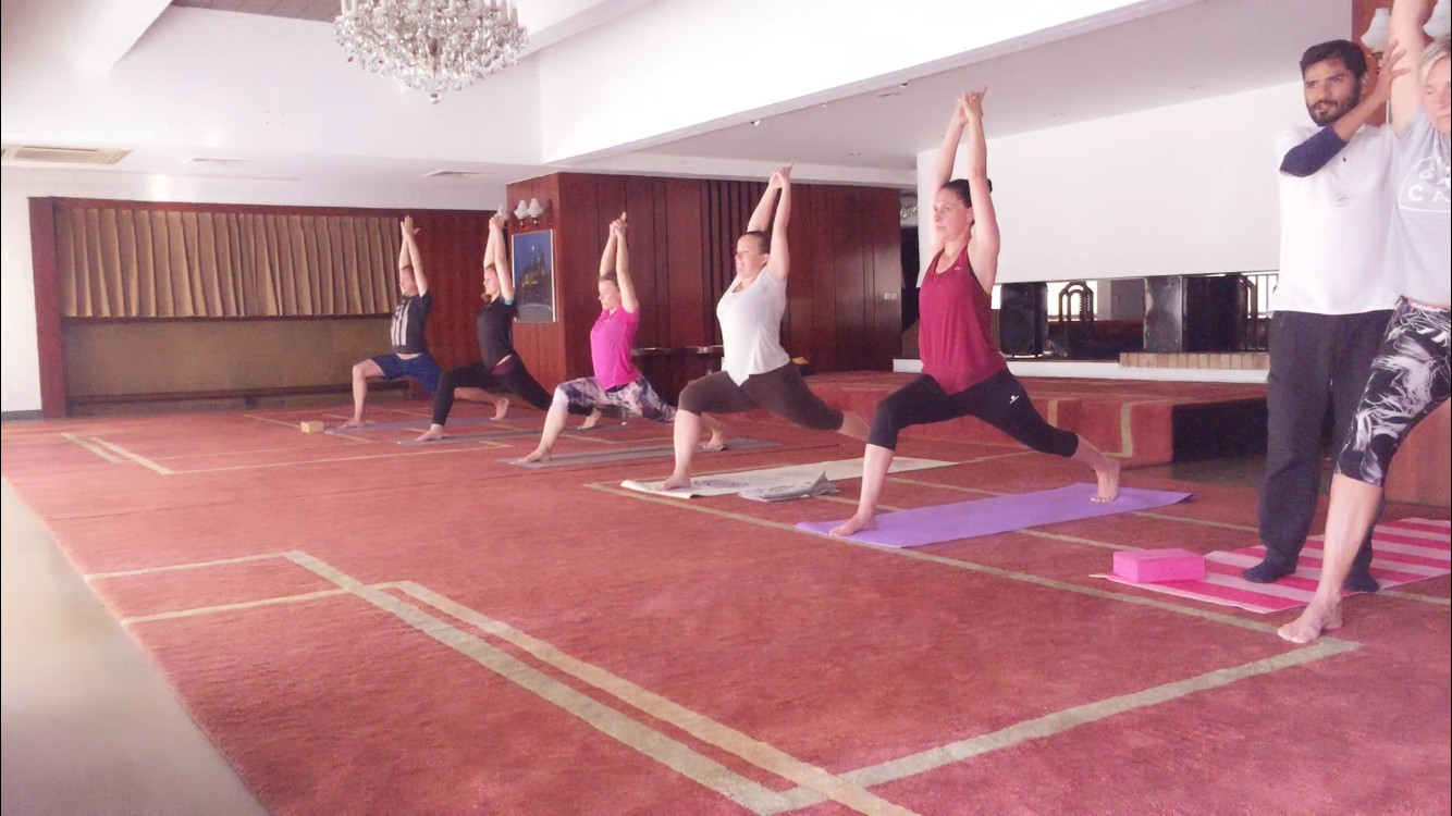 6 girls are doing yoga. and teacher helping them.